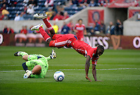 Chicago forward Patrick Nyarko (14)  is sent flying by New England goalkeeper Matt Reis (1).  Chicago was awarded a penalty kick on the play.  The Chicago Fire defeated the New England Revolution 3-2 at Toyota Park in Bridgeview, IL on Sept. 25, 2011.