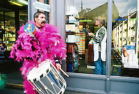 "Switzerland. Basel. Fasnacht Carnival. ""Clique""  is a group of persons playing music in the streets during the three days of the Fasnacht Carnival. A man dressed with pink feathers takes a brake while a woman working in a chemist shop arranges various drugs. © 1997 Didier Ruef"
