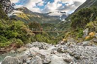 Wild Tekano Creek with trampers on swingbridge near Douglas Rock Hut in Copland Valley at sunrise, Westland Tai Poutini National Park, West Coast, South Westland, UNESCO World Heritage Area, New Zealand, NZ