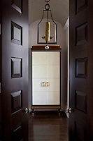 Double doors open onto a contemporary cupboard and a brass chandelier in the hallway