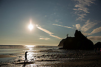 Lori walks in the wet sand at Ruby Beach, just north of Kalaloch in Olympic National Park, Washington on July 20, 2016. Behind her in the distance are sea stacks, rock formations that are remnants of  former headlands that the winds and waters of the Pacific Ocean have since eroded into stacks of rock standing at the beach. The sea stack in the distance with trees growing on it is called Abbey Island.