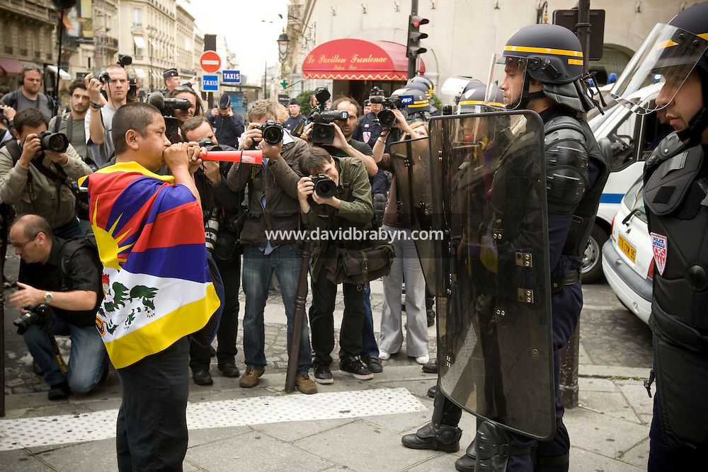 A man confronts a riot police cordon blocking access to the Chinese embassy in Paris, France, as press photographers work during a street protest called by press watchdog Reporters Sans Frontieres against China's human rights policy on the day of the opening ceremony of the 2008 Olympic Games in Beijing, 8 August 2008.