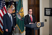 US President Donald J. Trump (L) listens as Secretary of Treasury Steven Mnuchin (R) delivers remarks in the US Treasury Department building in Washington, DC, USA, 21 April 2017. President Trump is making his first visit to the Treasury Department for a memorandum signing ceremony with Secretary Mnuchin.<br /> Credit: Shawn Thew / Pool via CNP /MediaPunch