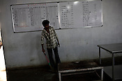 Rate list is seen on the board as the Indian worker sweeps the floor of the dining hall of the Chinese colony of Adani Power plant in Mundra port industrial city of Gujarat, India. Indian power companies have handed out dozens of major contracts to Chinese firms since 2008. Adani Power Ltd have built elaborate Chinatowns to accommodate Chinese workers, complete with Chinese chefs, ping pong tables and Chinese television. Chinese companies now supply equipment for about 25% of the 80,000 megawatts in new capacity.