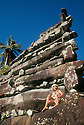Nan Douwas, the main structure at Nan Madol, an ancient social, political and religious complex constructed of basalt columns between 1100-1500 AD; (with Pohnpeian woman sitting at base); Pohnpei, Micronesia.