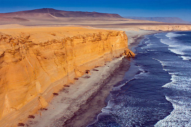 The desert and ocean come together along the cliffs of Playa Supay in the Paracas National Reserve, a subtropical coastal desert in Peru.