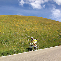 A lone cyclist descends the precipitous slopes of Passo delle Erbe, in the heart of the Dolomites, Südtirol (South Tyrol), Italy. Also known as Würzjoch (and in Ladin as Jü de Börz) the 2003 meter high mountain pass connects the city of Brixen in the Eisacktal with San Martin de Tor in the Val Gardena.