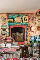 The colourful living room is furnished with Asian pieces, such as the Goan wooden armchair by the fireplace and the Indonesian bed which functions as a coffee table