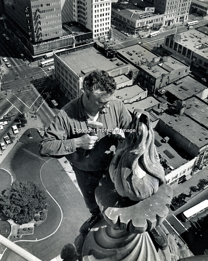 Seemingly indifferent to his perch more than 300 feet above the city, Bob Booth chips away at a decorative piece high on the Oakland. California  City Hall.He works for ABCO Waterproofing Co. who has a contract to repair and waterproof the building. (May 18, 1965 photo by Ron Riesterer)