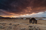 A forsaken log structure sits along Highway 569 with the Anaconda range seen in the background at sunset.