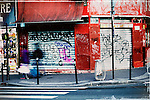 Fast walking pedestrians passing a traffic light in the Montmartre district of Paris with street art and posters on the walls.