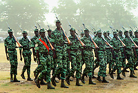 Soldiers carrying rifles on their shoulders marching in an Independence Day parade in Banjul, Gambia.  One man stands head and shoulders above the rest. He is likely to be more than seven feet tall.