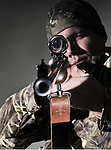 A hunter looks through the scope of his rifle.