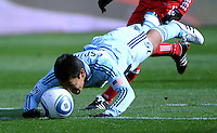 Sporting KC defender Roger Espinoza (15) gets a close look at the ball as he sends a diving header back to his goalkeeper.  The Chicago Fire defeated Sporting KC 3-2 at Toyota Park in Bridgeview, IL on March 27, 2011.