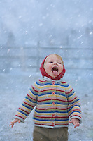 Young child, catching snowflakes on his tongue