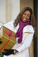Attractive young happy woman walking in an urban city environment and holding a Christmas gift wrapped in gold paper.