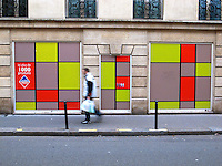 France. Paris. A single man walks on a sidewalk and passes near a colourful Leaderprice supermarket. Thousand products for sale. 17.11.10  &copy; 2010 Didier Ruef