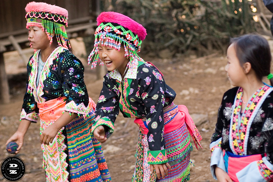 Young Hmong children wear colorful traditional clothing while playing a game called forfeit in the village of Sam Yord, in the county of Louang Namtha, Laos. This game is played with two rows of children who face each other. They throw a large, soft ball between them. If anybody lets the ball drop they have to pay a forfeit.  The remote village of Sam Yord, only accessible on foot, is a village of the Hmong ethnic group. Photograph by Douglas ZImmerman.