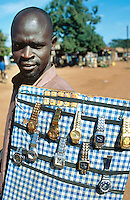 Uganda. Kayunga district. Baale. An itinerant dealer sells fake swiss gold and silver watches in the streets. He also has batteries for sale. © 2004 Didier Ruef