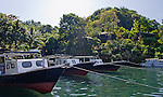 The Lembeh Resort's fleet of dive boats are moored in line, with guest rooms above.  In front of the Lembeh Resort, on Lembeh Island, off North Sulawesi, Indonesia.