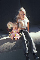 Two dolls interacting on car seat<br />