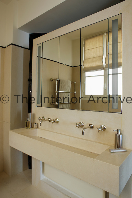 An air of timeless elegance has been achieved in the bathroom with a double basin, walls and floor created from the same cream-coloured stone