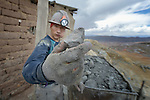 A miner displays a mineral-rich chunk of ore outside a mine in Potosi, Bolivia. The mine produces silver and other metals.