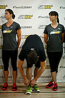 """Olympic medalist Michael Phelps ties his shoes next to his sisters  Whitney (L) and Hilary while they attend a event called """"Official Training Restaurant of the Phelps Family"""" to support his sister Whitney as she runs the ING New York City Marathon on November 4.  the event was organized by the food company """"Subway"""" in New York, United States. 15/10/2012. Photo by VIEWpress."""