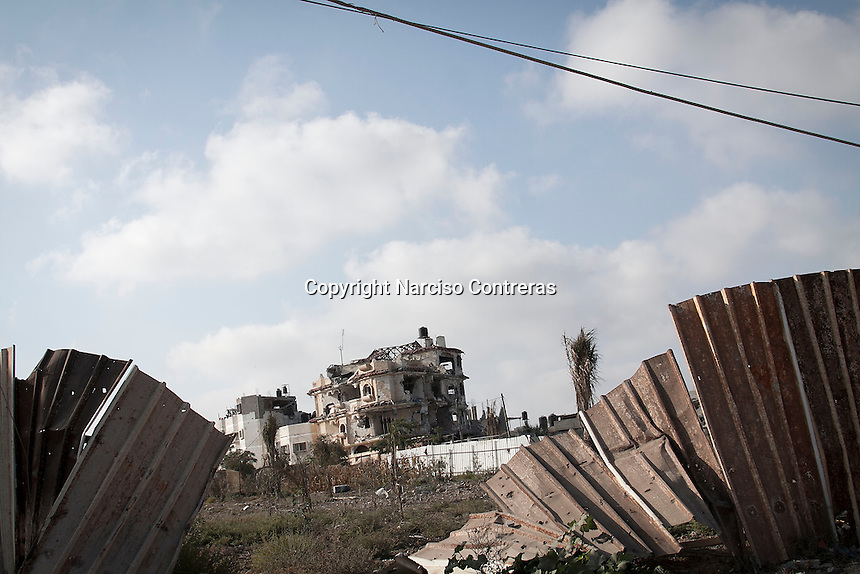 "In this Friday, Aug. 15, 2014 photo, a house building stands partially destroyed after artillery shelling hits Al-Khobar area during the ""Protective Edge"" Israeli military operation in Gaza Strip. (Photo/Narciso Contreras)"