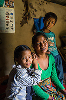 Kalpana Tamang (40), poses for a portrait with her younger daughter Binita (10) and son Sonam (7) in their temporary shelter in Kavre, Bagmati, Nepal on 30 June 2015.  Kalpana, a widow with 3 children, has been supported by SOS Children's Villages for many years now and had receive the Home-in-a-Box after the earthquake destroyed her house, almost killing her two daughters. She now lives in a temporary shelter, sharing her dwelling with farm animals, and is trying to make ends meet by weaving bamboo baskets to supplement the financial assistance provided by SOS Childrens Villages. The NGO mostly supports her children's welfare and schooling as well as provides her with essential household and schooling items like kitchen utensils and school books and uniforms. Photo by Suzanne Lee for SOS Children's Villages