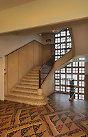Staircase and pebble mosaic floor resembling fabric design, in the hall of the Residence Lucien Paye, designed by Jean Vernon, Bruno Philippe and Albert Laprade, 1883-1978, and inaugurated 1949, in the Cite Internationale Universitaire de Paris, in the 14th arrondissement of Paris, France. Originally the Overseas French Territories House, the building was later used to house students from Sub-Saharan African countries. The CIUP or Cite U was founded in 1925 after the First World War by Andre Honnorat and Emile Deutsch de la Meurthe to create a place of cooperation and peace amongst students and researchers from around the world. It consists of 5,800 rooms in 40 residences, accepting another 12,000 student residents each year. Picture by Manuel Cohen. L'autorisation de reproduire cette œuvre doit etre demandee aupres de l'ADAGP/Permission to reproduce this work of art must be obtained from DACS.