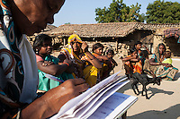Shanti Adivasi (in white saree), 52, interviews a family of tribal villagers in their housing compound in Manikpur, Chitrakoot, Uttar Pradesh, India on 4th December 2012.  Shanti used to be a wood gatherer, working with her parents since she was 3, and later carrying up to 100 kg of wood walking 12km from the dry jungle hills to her home to repack the wood which sold for 3 rupees per kg. After learning to read and write in an 8 month welfare course, at age 32, she became a reporter, joining Khabar Lahariya newspaper since its establishment in 2002, and making about 9000 rupees per month, supporting her family of 14 as the sole breadwinner. Photo by Suzanne Lee for Marie Claire France.