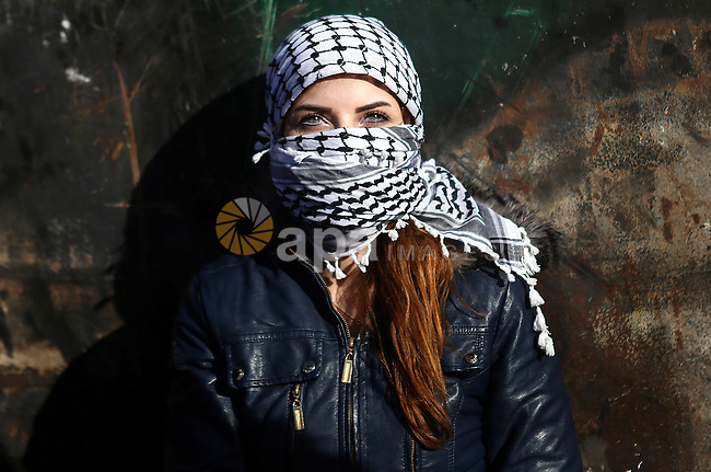 A female Palestinian protester takes a cover during clashes with Israeli troops near the Jewish settlement of Bet El, near the West Bank city of Ramallah, October 29, 2015. Israeli security forces shot dead two Palestinian assailants in the occupied West Bank on Thursday, police and the army said, as a month-long spate of stabbing attacks showed no signs of abating. Photo by Shadi Hatem