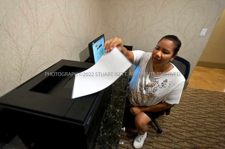 """9/27/2011--Seattle, WA, USA..Valerie Bayers, 34, from Vancouver, Canada, using the business center, just off the main lobby, at the Silver Cloud Hotel in Seattle, WASH. Bayers was visiting Seattle on vacation so did not have a laptop with her and needed to use the business center to print out information on a restaurant she wanted to visit...Business travelers armed with laptops, smartphones and wifi cards, are eschewing hotel business centers in favor of working in their rooms or the lobby, and hotels across the price spectrum have added the trappings of those business centers to where the guests are. Hotel business centers are still used by travelers who have a document or boarding pass to print, or need to check email and don't have their laptop, but they will usually get in and out quickly, rather than spend hours working there. And the business centers themselves are likely to be small rooms with just a few computers and printers. The Silver Cloud Hotel in Seattle, part of a ten-hotel chain in the Northwest, offers up two workstations and two printers, """"and business people barely use them,"""" said the hotel's general manager Chauncey DeVitis. The free WiFi and the copy machine behind the front desk seems to meet the needs of most business travelers these days, he said...©2011 Stuart Isett. All rights reserved."""