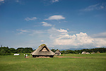 Visitors walk past reconstructions of pillar-suported buildings at Sannai-Maruyama, a large settlement  of the early to middle Jomon era, about 5,500 to 4,000 years ago, in Aomori Prefecture, Japan on 12 July 2011..Photographer: Robert Gilhooly