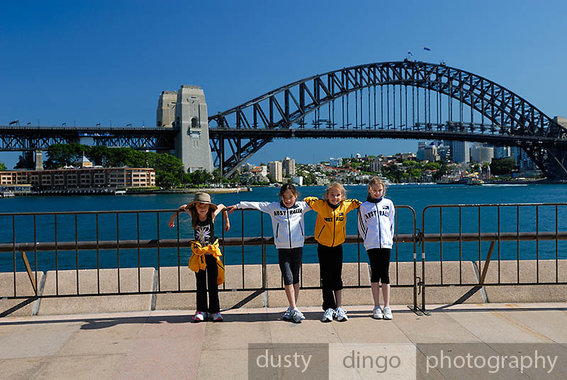 Four girls (one 6 year-old, three 10 year-olds), standing on Sydney Opera House concourse, with Sydney Harbour Bridge in background. Circular Quay, Sydney, Australia