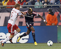 New England Revolution forward Dimitry Imbongo (92) on the attack as New York Red Bulls defender Markus Holgersson (5) closely defends. In a Major League Soccer (MLS) match, the New England Revolution (blue) tied New York Red Bulls (white), 1-1, at Gillette Stadium on May 11, 2013.