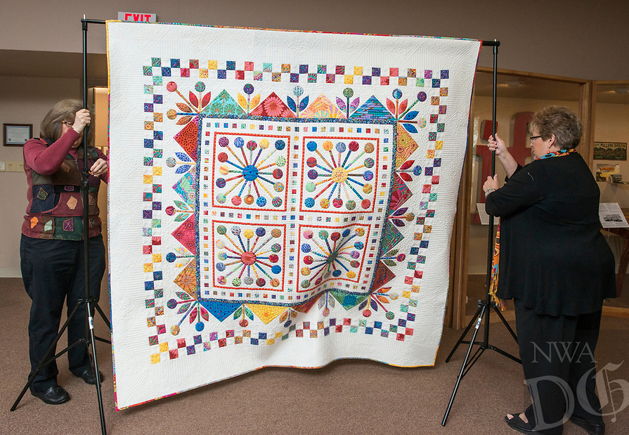 NWA Democrat-Gazette/ANTHONY REYES @NWATONYR<br /> Barbara Hamernik (left) and Adele Atha coordinator for Tomorrow's Heirlooms XVI quilt show, set up a winning quilts Monday, April 3, 2017 at the Shiloh Museum in Springdale.