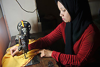 Seamstress working at a women's collective producing traditional clothing, Makassar, Sulawesi, Indonesia.
