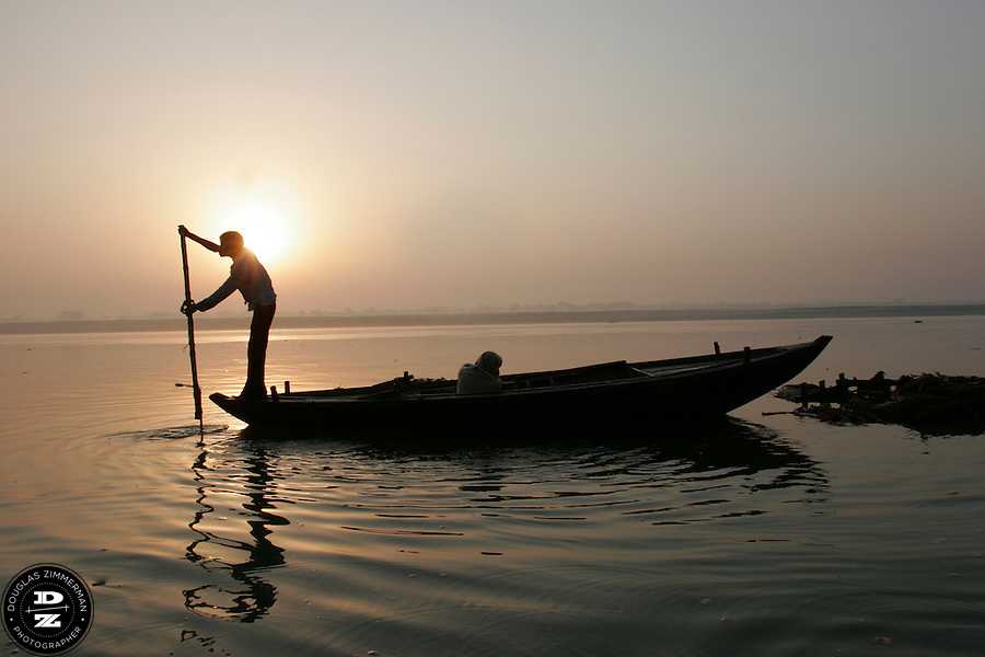 A man paddles a boat on the calm waters of  the Ganges (Ganga) River as the morning sun rises in the distance.  For Hindus, the Ganges is the most sacred river in India.  Hindus believe that the Ganges purifies all those who bathe in her waters, cleansing them of all their sins.  Photograph by Douglas ZImmerman