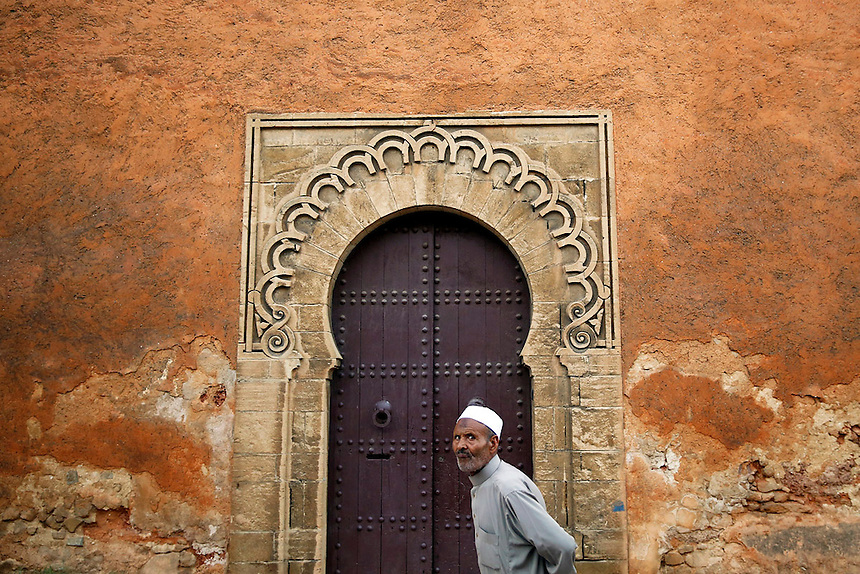 "A man walks in front of doors in walls of Rabat's Medina September 23, 2014. Behind walls of Medina and Kasbah of the Oudayas, ancient neighbourhoods of Morocco's capital, labyrinths of small alleys, colourful buildings and street markets offer a glimpse into city's rich history. Rabat was recently listed by UNESCO as a World Heritage Site and suggested as a ""must see"" destination by major media outlets and tourist agencies.  REUTERS/Damir Sagolj (MOROCCO)"