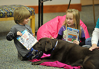 NWA Democrat-Gazette/Michael Woods --01/14/2015-- w @NWAMICHAELW... Wiggles, a therapy dog at the Springdale Library, nudges the book as Gabriel Stewart, age 4 (left) and Calie Becker, age 7, pick out books to read during Wednesday evenings session of the Kibbles and Books program at the Springdale Public Library. Kibbles & Books is a literacy program designed to build confidence in young readers by reading out loud to therapy dogs giving the children a chance to practice their literacy skills in a stress-free and fun context.