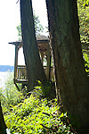 A private, hidden gazebo perched in the trees above this waterfront weekend vacation retreat on Washington State's Vashon Island boasts two chairs and a small outdoor cushioned bench for taking in the sunsets and views of the water.