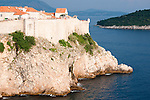 View of the old city walls of Dubrovnik, Croatia and the dramatic cliffs down to the sea and at sunet.
