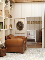 A child's bedroom can just be seen through an open door in the entrance hall where modern bookshelves line one wall