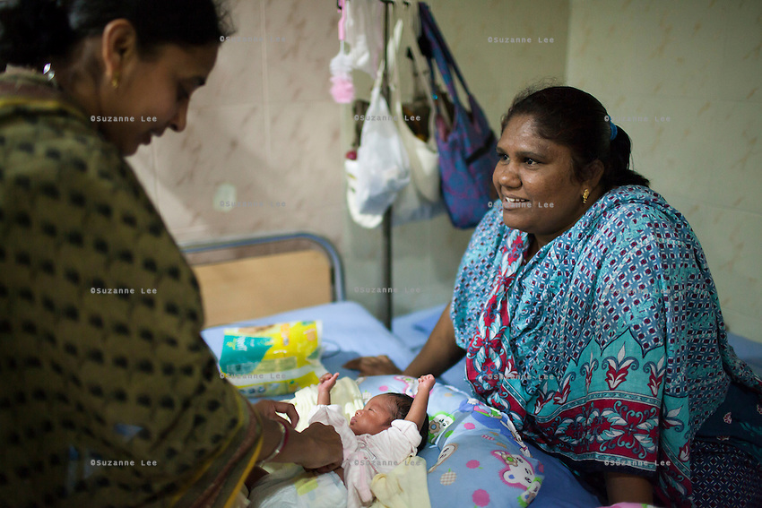 Manisha (right), an ex-surrogate, has continued to work with Dr. Patel's Akanksha clinic as a nanny for new-born test tube babies, like these twins in the Neonatal Intensive Care Unit (NICU) at the Apara Nursing Home, where babies from the Akanksha clnic are often sent for neonatal and other post-birth intensive care, in Anand, Gujarat, India on 10th December 2012. Manisha, a widow and mother of 3 of her own children, has taken care of over 100 babies for Dr Patel's surrogacy clients, making up to 15000 rupees per month. Photo by Suzanne Lee / Marie-Claire France