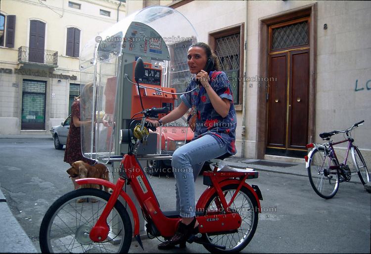 Mantova, ragazza con motorino Ciao a un telefono pubblico.<br /> Mantua, girl with scooter at a phone box.