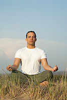 man in a yoga pose while on a sand dune in The Hamptons