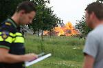 Foto: VidiPhoto<br /> <br /> ELST (Gld) - Een grote grijpmachine van loonbedrijf B. de Vree uit Dodewaard is woensdag nodig om in de buurt van Elst (Gld) de niet verkochte bomen, bamboestokken en snoeihout in de enorme vuurzee van boomkweker Combinatie Mauritz te werpen. Door het koude voorjaar hebben boomkwekers niet voor de deadline van 1 juni hun houtafval kunnen verwerken en geven de gemeenten Neder-Betuwe en Overbetuwe tot eind juli ontheffing voor het verbranden van de restanten. In beide gemeenten bevinden zich veel percelen van boomkwekers. Neder-Betuwe is daarin soepeler dan de buurgemeente. Waar bij de een een telefonische melding volstaat, moet bij de ander een offici&euml;le ontheffing aangevraagd worden. De Combinatie Mauritz is wat productie betreft de grootste laanboomkweker van Nederland en heeft in zowel Overbetuwe als Neder-Betuwe zo'n 150 ha. grond. Foto: Politiecontrole.