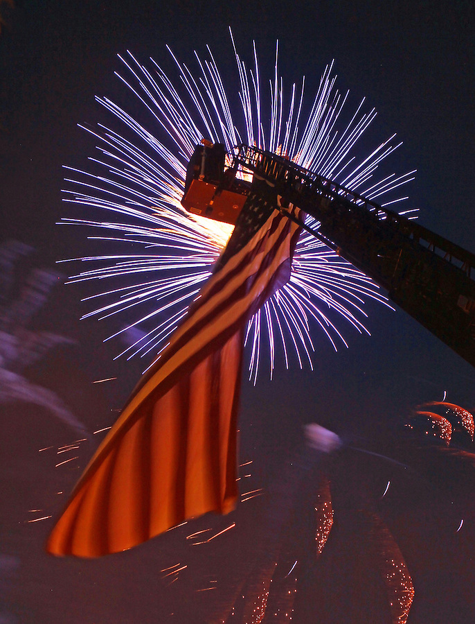 An American flag attached to a fire truck is illuminated by 4th of July fireworks display. Photo/Andrew Shurtleff